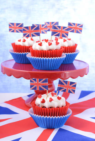 british foods: Holiday party cupcakes with UK flags on red cake stand with Union Jack flag.
