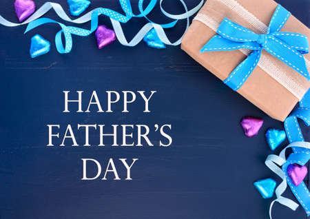 blue gift box: Happy Fathers Day background on dark blue distressed wood table with decorated borders.