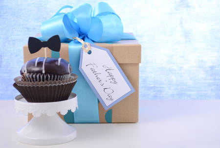 blue gift box: Happy Fathers Day cupcake gift on pale blue and white wood background. Stock Photo