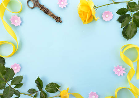 Summertime background with decorated borders of yellow roses, pink candy and yellow ribbon on pale blue wood table, with copy space.