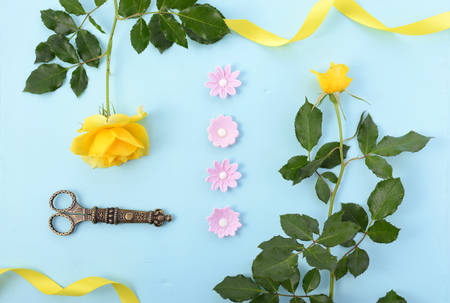 a stem here: Summertime background with decorated borders of yellow roses, pink candy and yellow ribbon on pale blue wood table, with copy space.