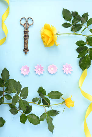 mothering: Summertime background with decorated borders of yellow roses, pink candy and yellow ribbon on pale blue wood table, with copy space.