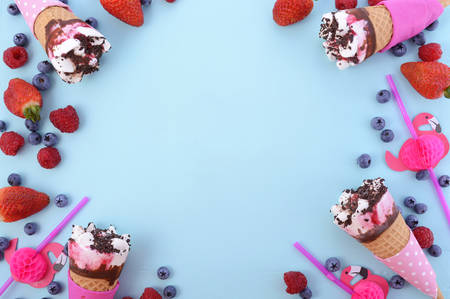 Pink and blue theme Summertime background with decorated borders of ice creams and berries on wood background. Banque d'images