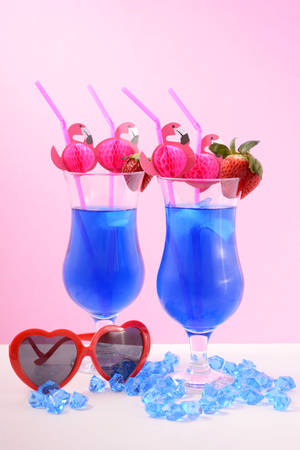 quirky: Summer is Here theme Blue Hawaiian cocktails with pink flamingo straws and quirky sunglasses Stock Photo