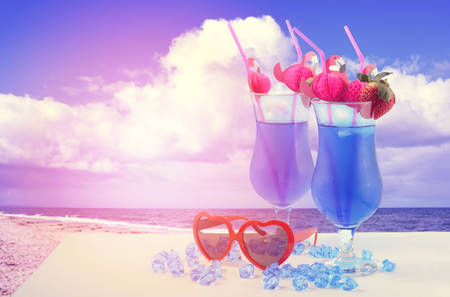 Summer is Here theme Blue Hawaiian cocktails with pink flamingo straws and quirky sunglasses