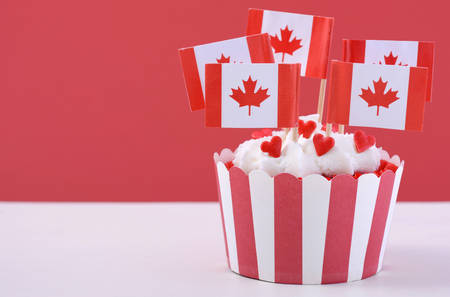 dominion: Happy Canada Day Party Cupcake with maple leaf flags on a white wood table against a red background. Stock Photo