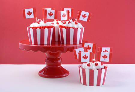 tortas de cumpleaños: Felices del día de Canadá de las magdalenas del partido en una torta roja de pie con banderas hoja de arce en una mesa de madera blanca y fondo rojo.