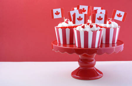 dominion: Happy Canada Day Party Cupcakes on a red cake stand with maple leaf flags on a white wood table and red background.