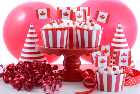 dominion: Happy Canada Day Party Cupcakes on a red cake stand with maple leaf flags on a white wood table with party balloons, hats and decorations. Stock Photo