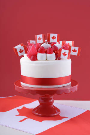 Happy Canada Day celebration cake with flags, marshmallow and candy decorations on a red cake stand on a white table against a red  background.