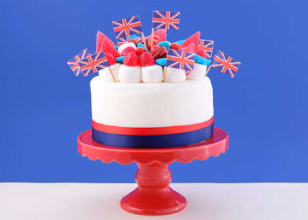 brit: UK celebration cake with flags, marshmallow and candy decorations on a red cake stand on a white table against a blue background.