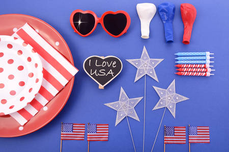 independance: Happy Fourth of July BBQ party plates, balloons, stars and flags flat lay in red, white and blue theme colors.