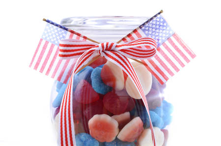 independance: Happy Fourth of July patriotic jar of red, white and blue candy with flags on a white background. Stock Photo