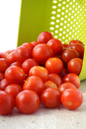 kitchen bench: Ripe red cherry tomatoes tumbling out of bright green colander on to kitchen bench top, vertical.