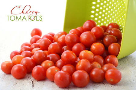 kitchen bench: Ripe red cherry tomatoes tumbling out of bright green colander on to kitchen bench top. Stock Photo