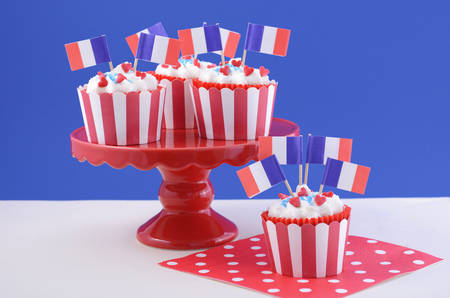 cakestand: Happy Bastille Day red, white and blue cupcakes on red cakestand on blue and white background.