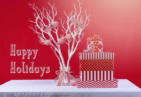 Christmas red and white gifts with modern white tree branch and ornamental birds on white table against a bright red background, with retro hand drawn style text and added light leaks filter.