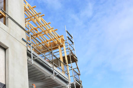 commercial construction: Partial construction on medium office commercial building showing scaffolding and new work against a blue sky, with copy space.