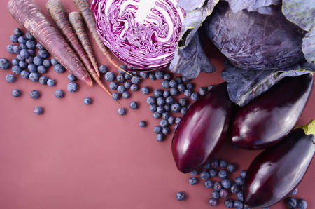 Purple fruits and vegetables thay contain Anthocynins, found in the Okinawan diet, that maintain healthy blood vessels and promote longevity, overhead with copy space. Banco de Imagens