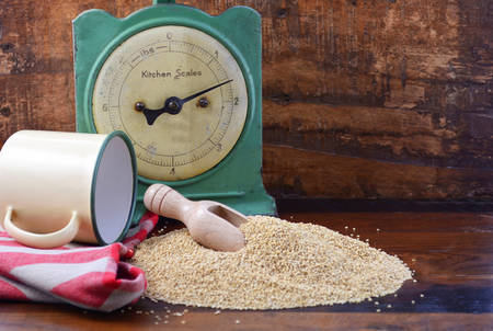 Pile of quinoa grain with wooden scoop with vintage kitchen scales and tin cup bowl on dark wood background, with copy space. Stock Photo