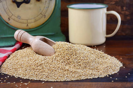 wooden scoop: Pile of quinoa grain with wooden scoop with vintage kitchen scales and tin cup bowl on dark wood background, closeup.