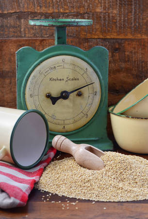 wooden scoop: Pile of quinoa grain with wooden scoop with vintage kitchen scales and tin cup bowl on dark wood background. Stock Photo