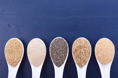 psyllium: Grains including, white grain quinoa, psyllium husk powder, black chia, wheat germ, and ground LSA mix, on dark blue wood grain table, with copy space.