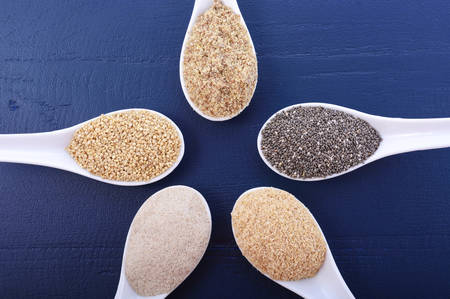 psyllium: Grains including, white grain quinoa, psyllium husk powder, black chia, wheat germ, and ground LSA mix, in white measuring spoons on dark blue wood grain table.