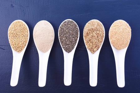 Grains including, white grain quinoa, psyllium husk powder, black chia, wheat germ, and ground LSA mix, in white measuring spoons on dark blue wood grain table.