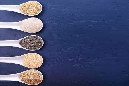 dark blue: Grains including, white grain quinoa, psyllium husk powder, black chia, wheat germ, and ground LSA mix, on dark blue wood grain table, with copy space.