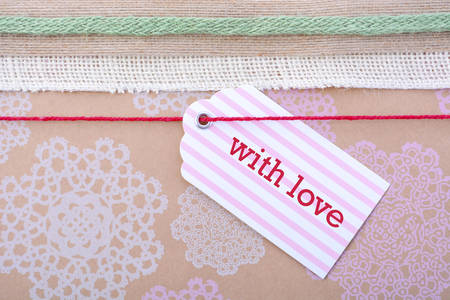 Close up of vintage gift wrapping with multiple ribbons and gift tag on floral stenciled natural brown paper.