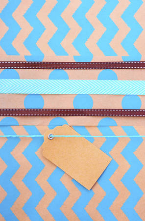 Modern holiday greeting background with close up of vintage gift wrapping with multiple ribbons and gift tag on aqua chevron striped natural brown paper.