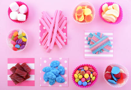 childrens birthday party: Bright colorful candy background on pink wood table for Halloween trick of treat or childrens birthday party favors.