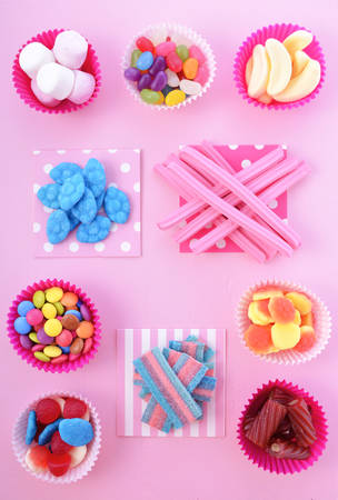 Bright colorful candy background on pink wood table for Halloween trick of treat or childrens birthday party favors.