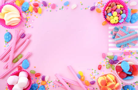 Background with decorated borders of bright colorful candy on pink wood table for Halloween trick of treat or childrens birthday party favors. Stock Photo