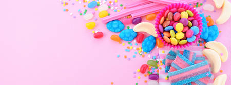 placeholder: Bright colorful candy background on pink wood table for Halloween trick of treat or childrens birthday party favors, sized to fit a popular social media cover image placeholder. Stock Photo