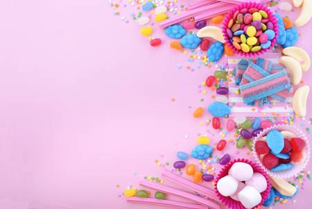 치료 또는 어린이 생일 파티 호의 할로윈 트릭 핑크 나무 테이블에 밝은 다채로운 캔디 장식 된 테두리가있는 배경. 스톡 콘텐츠