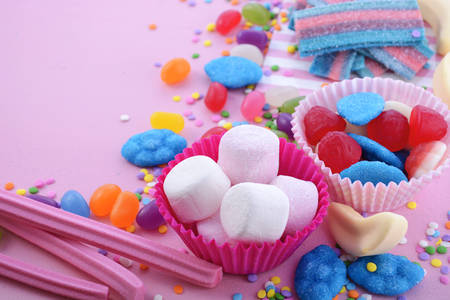 childrens birthday party: Bright colorful candy background on pink wood table for Halloween trick of treat or childrens birthday party favors, closeup. Stock Photo