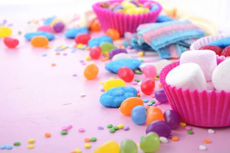 治療や子供の誕生日パーティー、クローズ アップのハロウィーンのトリックのためのピンクの木製テーブルの背景を明るいカラフルなキャンディ。 写真素材