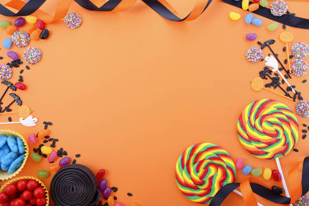 Halloween or Childrens Birthday candy favors on a bright orange background with decorated borders and copy space. Imagens - 60927247