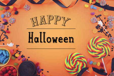 Halloween candy favors on a bright orange background with decorated borders and copy space, with applied filters and added Happy Halloween text.
