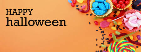 placeholder: Halloween or Childrens Birthday candy favors on a bright orange background sized to fit a popular social media cover image placeholder. Stock Photo
