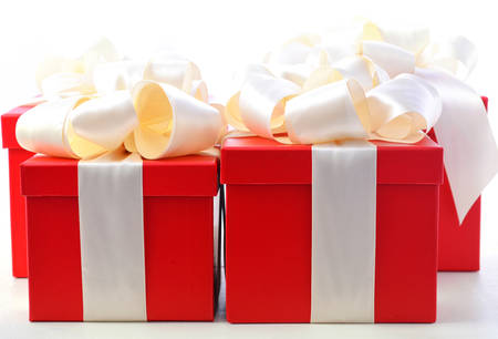 beautifully wrapped: Bright red festive holiday gift boxes beautifully wrapped in cream white satin ribbon, on white wood table