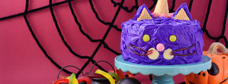 Happy Halloween cat cake party food with purple frosting, sized to fit a popular social media cover image placeholder.