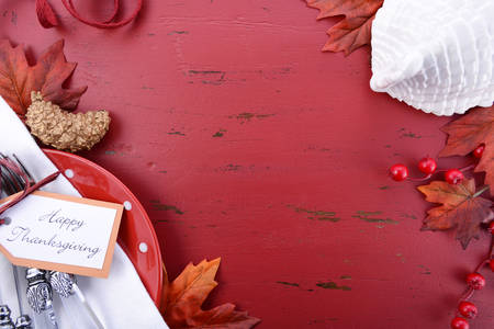 Red and white theme Thanksgiving background with decorated borders on a distressed red wood table, with a white turkey tureen and table setting. Stock Photo