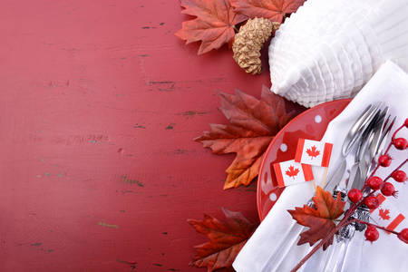 canadian maple leaf: Canada red and white theme Thanksgiving background with decorated borders on a distressed red wood table, with a white turkey tureen and Canadian Maple Leaf Flag. Stock Photo