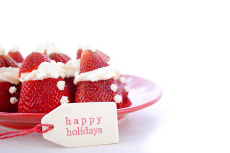 cute christmas: Strawberry Santas on red and white polka plate on a white wood table with Happy Holidays gift tag for fun, cute Christmas festive party food. Stock Photo