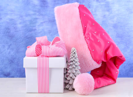 ladylike: Feminine Christmas twist with Female Santa Hat with pink and white gift box on white table against a modern blue and white background. Stock Photo