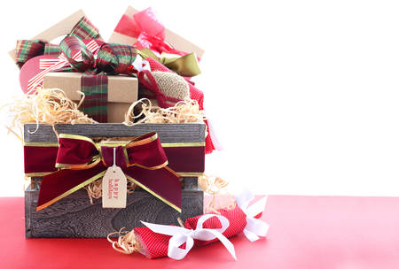 hamper: Large Christmas gift hamper with traditional red and green wrapping on red wood table, with copy space. Stock Photo