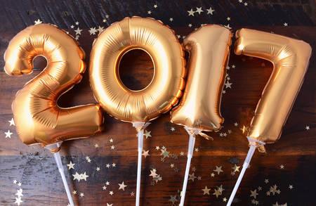 nombre d or: Happy 2017 or Ballons de nouvel an avec des étoiles scintillantes sur fond de table en bois foncé.